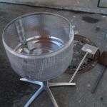 In einer ehemaligen Wäschetrommel wird die Grillkohle vorgeglüht.